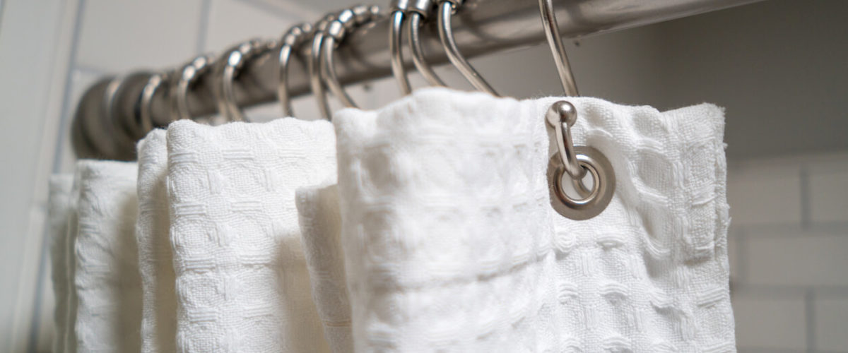 white shower curtain on rings