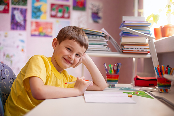 Child smiling at their homeschool desk