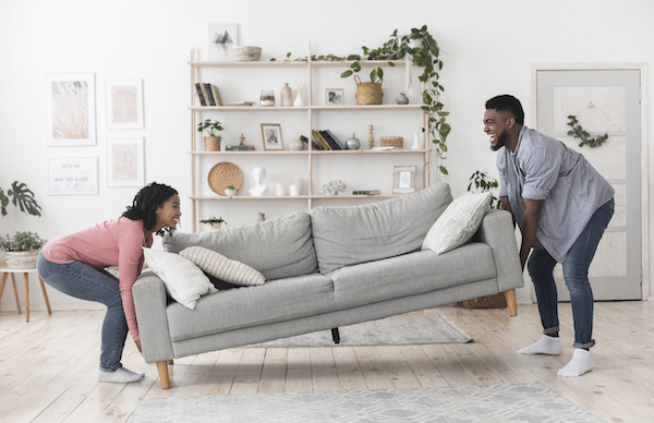Black couple moving a sofa in their home. Both people seem to be having a good time.
