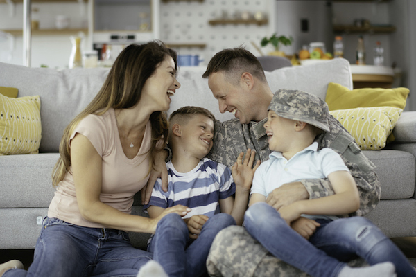 Soldier sitting in front of a couch with his wife and kids.