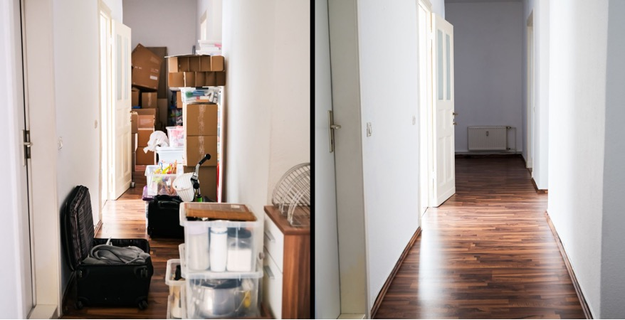 collection of stacked boxes in a hallway. There is also an open suitcase in the foreground of the photo.