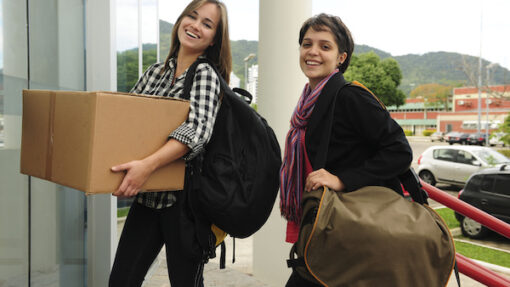 Two smiling students walking toward a building with a cardboard box