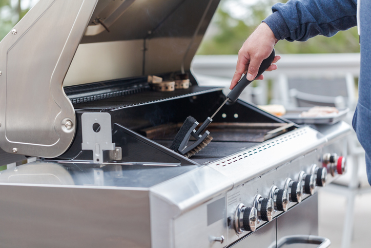 man scrubbing down grill grates with a brush