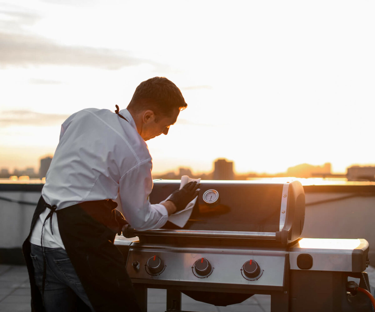 man cleaning a grill with a cloth