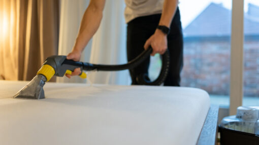 A man vacuuming dirt and dust from a bare mattress in a bedroom