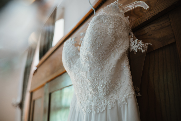 a white wedding dress hanging on the door of a closet